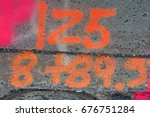 Small photo of Number one hundred twenty-five painted on cracked asphalt