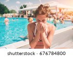 Small photo of picture from a Beautiful women in bikini with handkerchief. Sick female model has runny nose. girl makes a cure for the common cold. She is sick in the summer on vacation