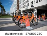 Small photo of Orlando, Florida USA-April 29, 2017: Public rental bikes lined up in front of The Beacon and Code Wall parking structure by artists Jefre Manuel and Michael Counts in Lake Nona Town Center Florida