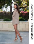 Small photo of Pretty brunette in tan pantyhose, sweater and open toe heels looking coy in courtyard.