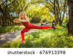 Small photo of Three joyful healthy women are engaged in fitness on a sports suspension device on the ground under a tree in the open air group of cheerful attractive women are engaged in sports.