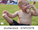 a baby is hungrily eating a... | Shutterstock . vector #676915378