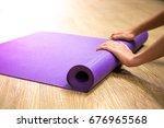woman rolling her mat after a... | Shutterstock . vector #676965568