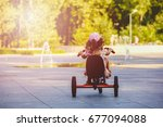 Little girl with a tricycle in...