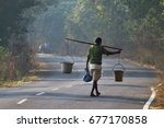 A Village Man Carrying Two...