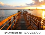 Small photo of Van Zant Pier after a rainstorm in Newport, Rhode Island. The wooden platform is wet from the rain, during the sunset. In the background is the Newport Bridge and storm clouds. Popular with fishermen