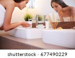 young woman washing her face... | Shutterstock . vector #677490229