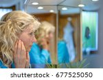 Small photo of Middle-aged woman looking at herself in a mirror with her hands to her cheeks as she considers the ageing process with multiple reflections