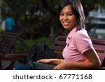 A cute college student wearing pink shirt smiling with laptop on lap outside sitting on a university campus bench.  20s female Asian Thai model of Chinese descent looking over shoulder at camera - stock photo