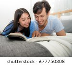 reading a book together on bed... | Shutterstock . vector #677750308