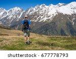 man hiker goes along alpine... | Shutterstock . vector #677778793