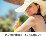 woman apply suntan lotion | Shutterstock . vector #677828104