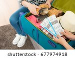 Small photo of selective focus photo of two female people organized personal luggage and packing travel suitcase at home and showing boarding card.