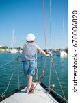 Small photo of dreaming kid captain aboard luxury yacht looking forward