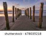 old jetty posts at sunrise on... | Shutterstock . vector #678035218