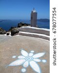 Small photo of Aegean sea view from Santorini island with an arty flower drawn on the soil on the foreground