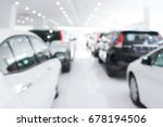 A row of new cars parked at a car dealership stock blurry - stock photo