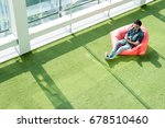 Small photo of Man use smartphone on bean bag in afternoon, freelance conceptual lifestyle, internet in everyday life