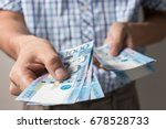 Small photo of Photo of hands holding bundle of blue money in cash of one thousand philippines peso as if being rich, boastful. Show off, pay bills or give bribe. Payment procedure