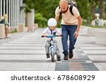 Small photo of First lessons bicycle riding. Father teach his son to ride a bike.