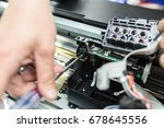 Man's hand twist screw by screwdriver in printer. Closeup, focus at screw in the center.  - stock photo