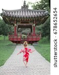 Small photo of Small toddler redhead girl in traditional Japan National Costume yukata run on the background of Asian alcove. multicultural society concept
