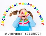 Small photo of Happy preschool child learning to read and write playing with colorful roman alphabet letters.