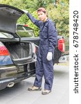 Small photo of Young mechanic in uniform replacing while changing tires on a vehicle to replace the spare tire at the back of the car.