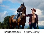 Macho man handsome cowboy and horse on the background of sky and water. Western style.  - stock photo