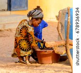 Small photo of FERLO DESERT, SENEGAL - APR 25, 2017: Unidentified Fulani woman washes dishes in the basin on the street. Fulanis (Peul) are the largest tribe in West African savannahs