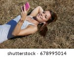woman with cellphone in meadow | Shutterstock . vector #678995014