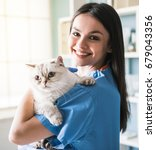 Stock photo beautiful young veterinarian is holding cute cat looking at camera and smiling while standing in 679043356