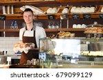 handsome male baker in black... | Shutterstock . vector #679099129