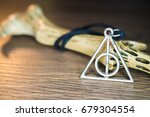 Small photo of Deathly Hallows Angels Necklace of Amulets,Wizards amulet on wooden table, Wizard tool.