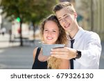 young couple selfy on street | Shutterstock . vector #679326130