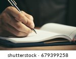 male hand with pen writing in... | Shutterstock . vector #679399258