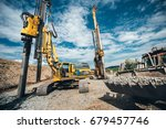 Highway construction site with heavy duty machinery. Two Rotary drills, bulldozer and excavator working  - stock photo