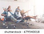 Small photo of Cheerful colleagues having fun in office chairs