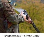 gunman with smoking shotgun after a shot