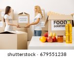 Small photo of Nice altruistic woman helping her colleague with heavy box