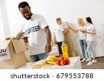 Small photo of Energetic altruistic man helping packing supplies