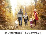 Stock photo family of four people walking a dog in forest 679599694
