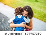 a woman hugs a curly haired boy ... | Shutterstock . vector #679967350