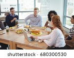 Stock photo business colleagues discussing while sitting around breakfast table at office cafeteria 680300530