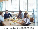 Stock photo high angle view of business people having lunch on table at office cafeteria 680365759