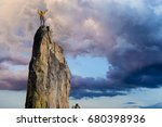 Small photo of Male climber celebrates on the summit of a sheer rock spire.