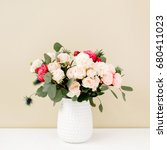 Small photo of Beautiful flowers bouquet: bombastic roses, blue eringium, eucalyptus branches in flowerpot at pale pastel beige wall. Floral lifestyle composition.