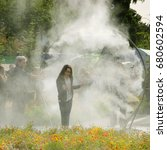 Small photo of PARIS, FRANCE - JUNE 4, 2017 - Girl enjoying passing through sprinkler water circle during BiodiversiTerre event (created by Gad Weil) showing relationship of man and nature in today's society.