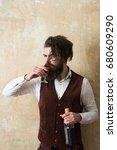 Small photo of Man drinking glass of wine. Brutal hipster with long beard and messy hair holding bottle on beige wall. Depression. Alcohol abuse and alcoholism. Addictive. Convive. Unhealthy lifestyle. Bad habits