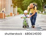 father help his son ride a... | Shutterstock . vector #680614030